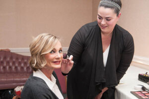 woman gets her makeup done before walking the stage