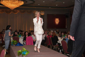 woman in white pant suit walks stage