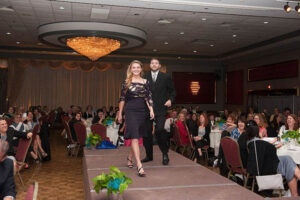 woman in black dress walks the stage as her date looks on