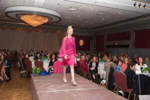 woman in hot pink dress walks stage