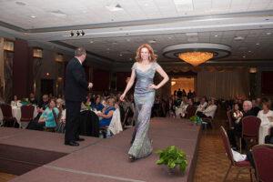 woman in silver dress walks stage