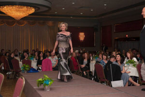 woman in off the shoulder dress walks the stage