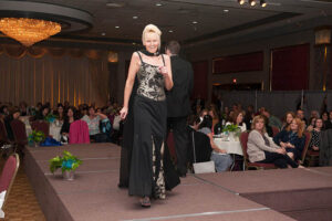 woman in black and metallic gown walks the stage