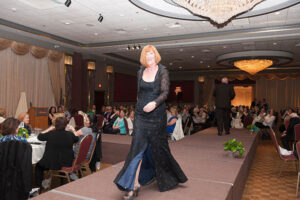 woman in evening gown walks the stage