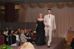 couple walks on stage, black dress and tan suit