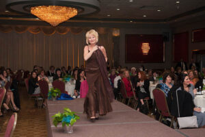woman in brown evening gown walks on stage