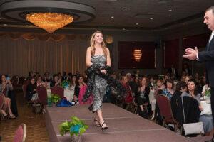 woman wearing patterned dress walks on stage