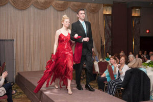 couple walks on stage, red dress with tux