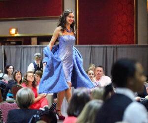woman walks on stage in blue dress
