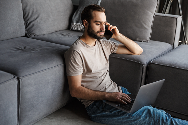 man in living room connects on phone and computer