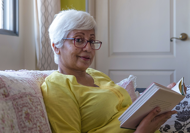 woman sits on couch with book